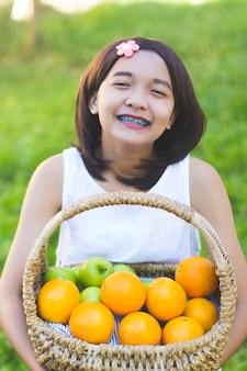 Glückliches junges asiatisches mädchen halten orange korb im garten.