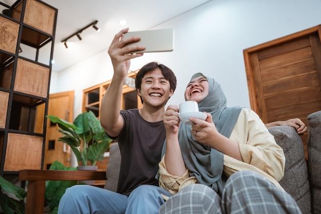 Glückliches junges asiatisches paar, das selfies unter verwendung einer smartphone-kamera beim scherzen und genießen des kaffees im wohnzimmer nimmt