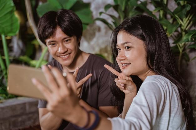 Glückliches junges asiatisches paar, das spaß hat und selfie-porträt auf hausgarten im freien bei nacht auf pflanzen nimmt