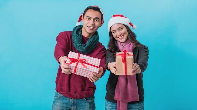 Glückliches junges asiatisches paar, das weihnachtsgeschenkboxen mit glücklichem lächelndem gesicht lokalisiert auf blau hält