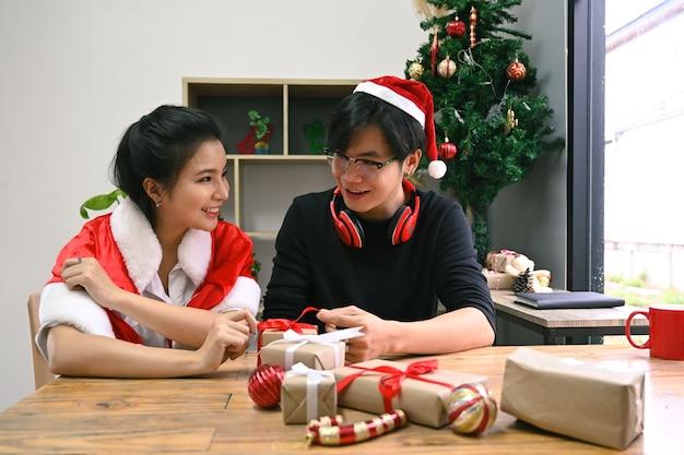 Glückliches junges asiatisches paar, das zusammen weihnachtsgeschenke im wohnzimmer zubereitet.