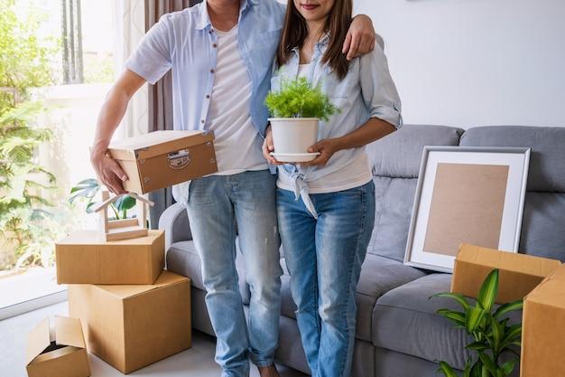 Glückliches junges asiatisches paar im wohnzimmer am neuen haus mit stapel von pappkartons am umzugstag
