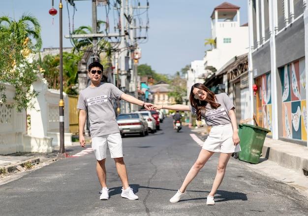 Glückliches junges asiatisches paar in der liebe, die an der straße aufwirft