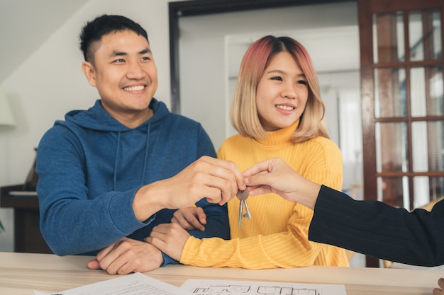 Glückliches junges asiatisches paar und grundstücksmakleragent