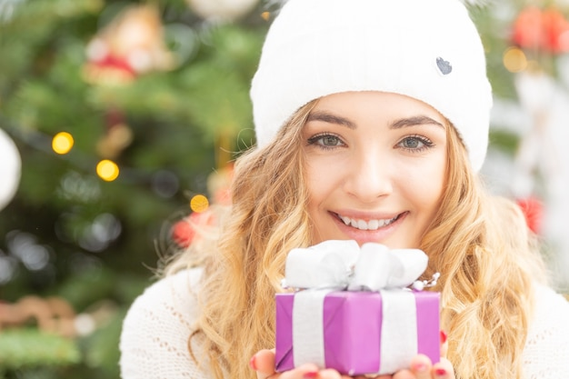 Glückliches junges blondes mädchen hält ein gut verpacktes geschenk mit einem weihnachtsbaum hinter sich.