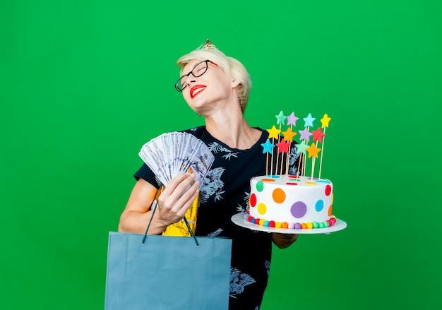 Glückliches junges blondes parteimädchen, das brille und geburtstagskappe hält, die geburtstagstorte mit sternengeld-geschenkbox und papiertüte hält, die mit geschlossenen augen auf grünem hintergrund mit kopienraum lokalisiert lächeln