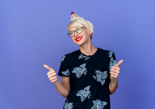 Glückliches junges blondes partygirl, das brille und geburtstagskappe trägt, die kamera zeigt, die daumen oben lokalisiert auf lila hintergrund mit kopienraum zeigt