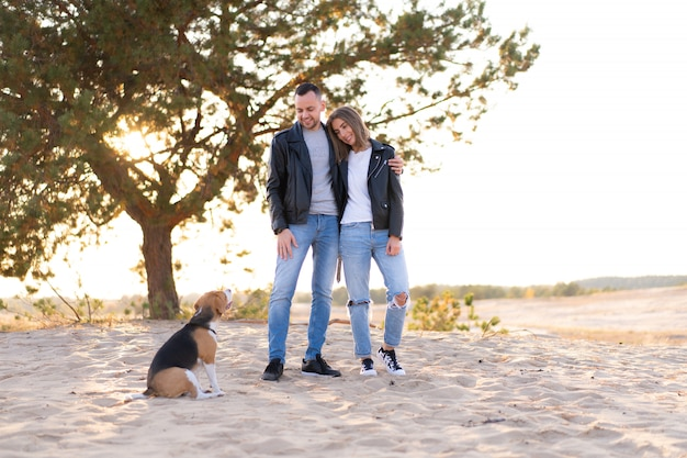 Glückliches junges erwachsenes kaukasisches paar mit hund beagle im freien