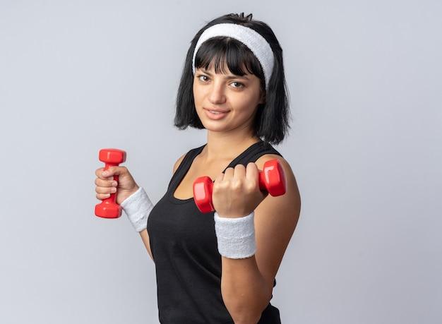 Glückliches junges fitness-mädchen mit stirnband, das hanteln hält und übungen macht, die selbstbewusst auf weißem hintergrund aussehen