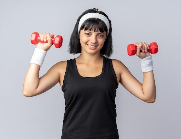 Glückliches junges fitness-mädchen mit stirnband, das hanteln hält und übungen macht, die selbstbewusst lächelnd aussehen