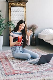 Glückliches junges frauöffnungsgeschenk vor laptop während videoanruf oder chat, geburtstag online feiern.