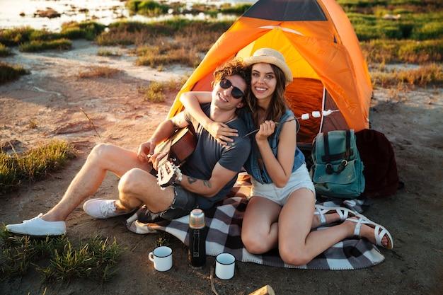 Glückliches junges fröhliches paar, das spaßcamping an einem see hat