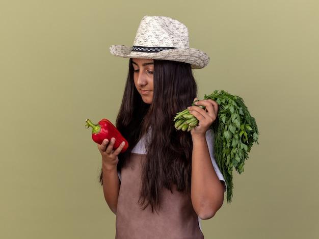 Glückliches junges gärtnermädchen in der schürze und im sommerhut, die frischen roten paprika und frische kräuter halten, die pfeffer mit interesse betrachten, der über grüner wand steht