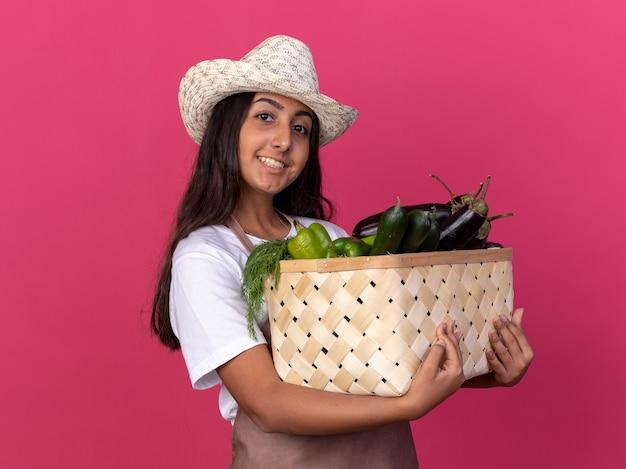 Glückliches junges gärtnermädchen in der schürze und im sommerhut, die kiste voll des gemüses mit lächeln auf gesicht halten, das über rosa wand steht