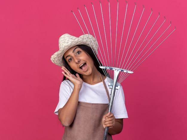 Glückliches junges gärtnermädchen in der schürze und im sommerhut, die rechen mit lächeln auf gesicht halten, das über rosa wand steht