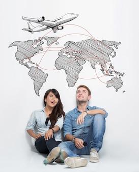 Glückliches junges gemischtes paar, das zusammen auf dem boden sitzt und sich vorstellt, eine reise um die welt zu haben
