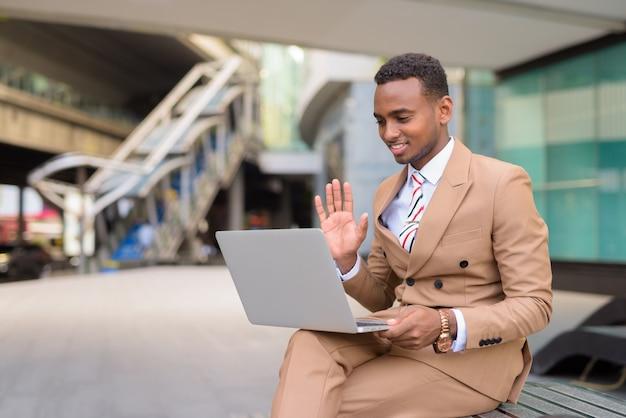 Glückliches junges hübsches afrikanisches geschäftsmannvideo, das mit laptop beim sitzen in der stadt im freien anruft