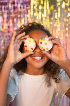 Glückliches junges hübsches mädchen an der festlichen partei, die cupcakes hält