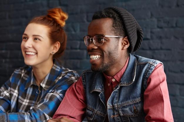 Glückliches junges interracial paar, das spaß hat, redet und lacht