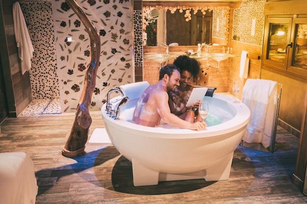 Glückliches junges interracial paar entspannte sich und genoss sich im whirlpool, trank wein und mit einer tablette