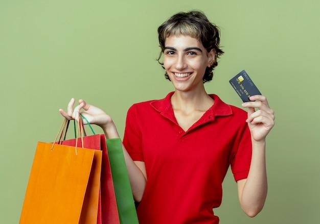 Glückliches junges kaukasisches mädchen mit pixie-haarschnitt, das einkaufstaschen und kreditkarte auf olivgrünem grün hält