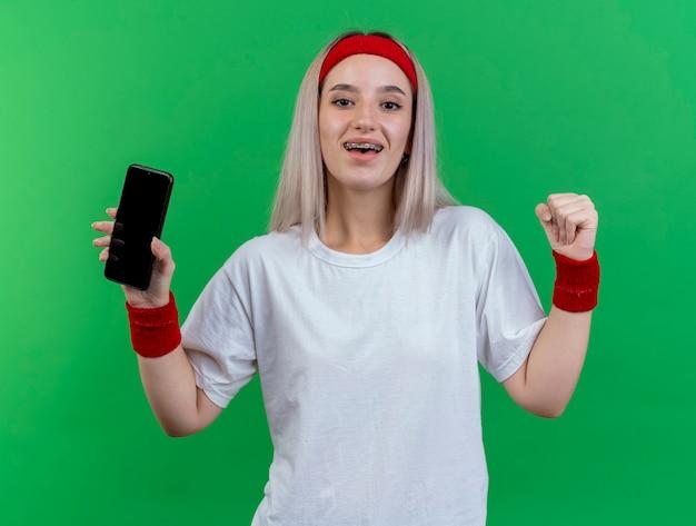 Glückliches junges kaukasisches sportliches mädchen mit hosenträgern, das stirnband und armbänder trägt, hält die faust und hält das telefon
