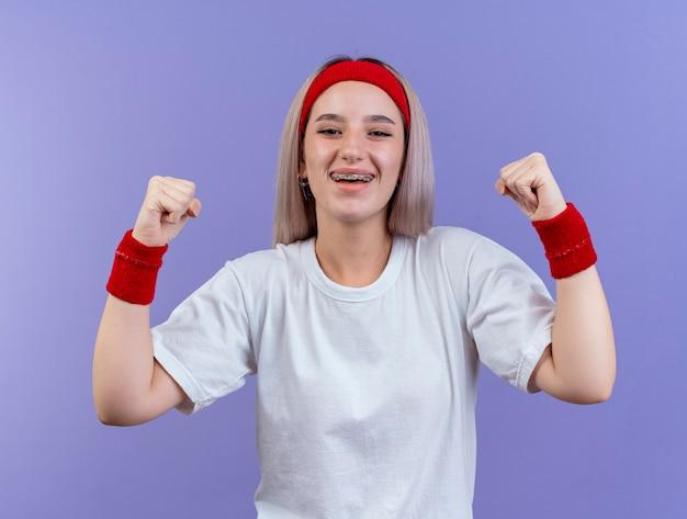 Glückliches junges kaukasisches sportliches mädchen mit hosenträgern, das stirnband und armbänder trägt, hält fäuste