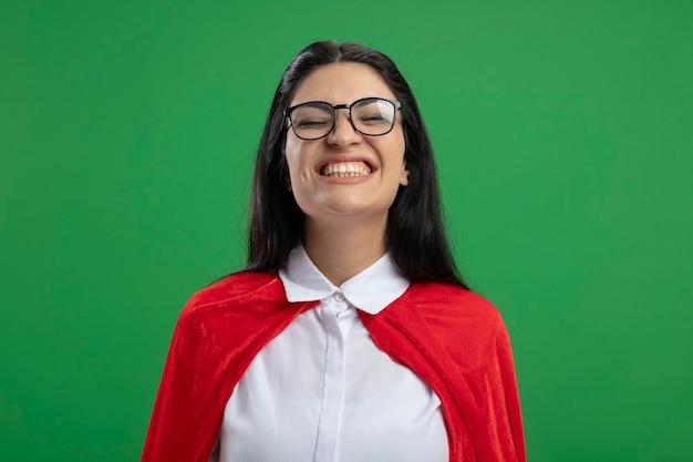 Glückliches junges kaukasisches superheldenmädchen, das eine brille trägt, die ohne irgendwelche bewegungen mit geschlossenen augen lächelt, lokalisiert auf grüner wand mit kopienraum