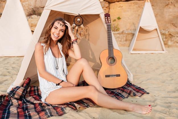 Glückliches junges lächelndes mädchen auf dem campingplatz am strand