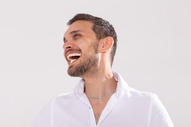 Glückliches junges lässiges mannporträt lokalisiert auf weißer wand