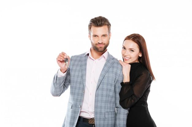 Glückliches junges liebendes paar, das schlüssel hält.