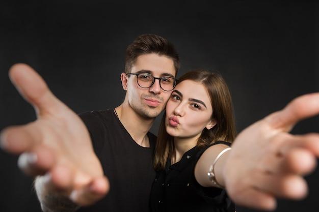 Glückliches junges liebendes paar, das selfie macht und lächelt, während gegen schwarzen hintergrund stehen