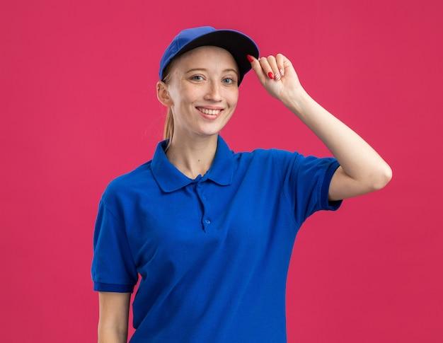 Glückliches junges liefermädchen in blauer uniform und mütze, das zuversichtlich lächelt