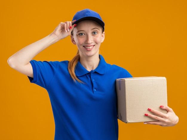 Glückliches junges liefermädchen in blauer uniform und mütze mit karton, das zuversichtlich lächelt