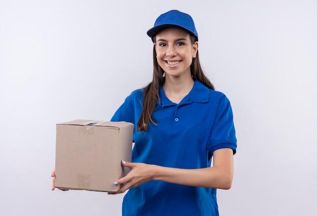 Glückliches junges liefermädchen in der blauen uniform und in der kappe, die boxpaket hält, das zuversichtlich lächelt