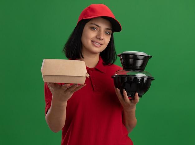 Glückliches junges liefermädchen in der roten uniform und in der kappe, die lebensmittelpakete hält, die freundlich lächelnd über grüner wand stehen