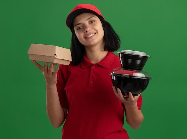 Glückliches junges liefermädchen in der roten uniform und in der kappe, die lebensmittelpakete lächelnd freundlich stehend über grüner wand halten