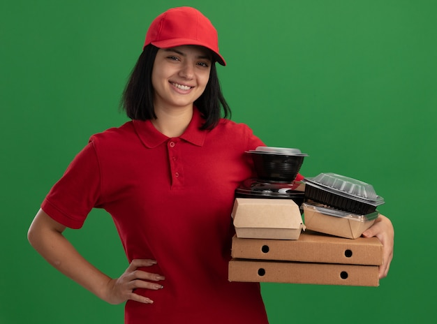Glückliches junges liefermädchen in der roten uniform und in der kappe, die pizzaschachteln und lebensmittelpakete hält, die fröhlich über grüner wand stehend lächeln