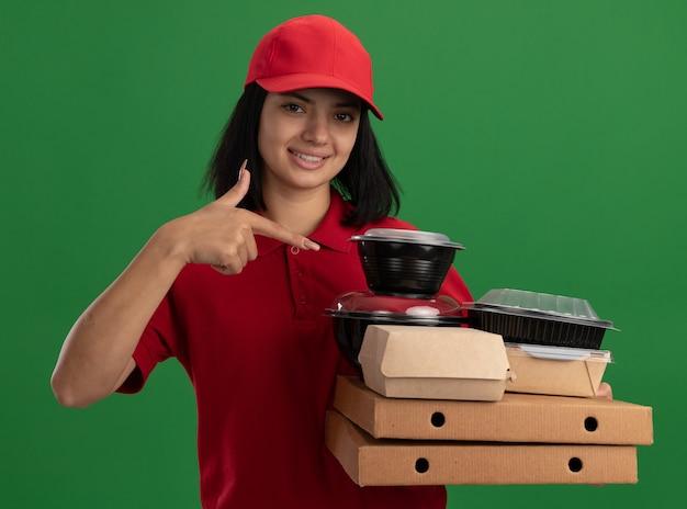 Glückliches junges liefermädchen in der roten uniform und in der kappe, die pizzaschachteln und lebensmittelpakete halten, die mit zeigefinger auf sie lächelnd stehen über grüner wand zeigen