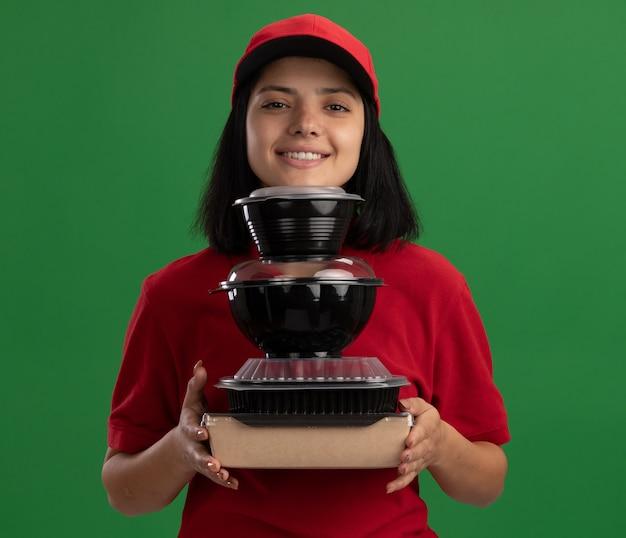 Glückliches junges liefermädchen in der roten uniform und in der kappe, die stapel der lebensmittelpakete hält, die freundlich lächelnd über grüner wand stehen
