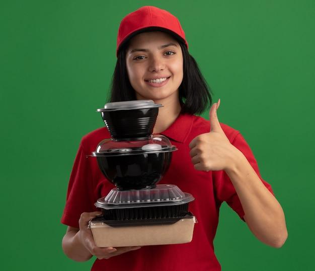 Glückliches junges liefermädchen in der roten uniform und in der kappe, die stapel der lebensmittelverpackungen hält, die freundlich lächelnd daumen hoch über grüner wand zeigend halten