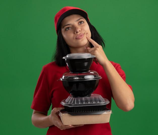 Glückliches junges liefermädchen in der roten uniform und in der kappe, die stapel von lebensmittelpaketen hält, die beiseite schauen, verwirrt über grüner wand stehend