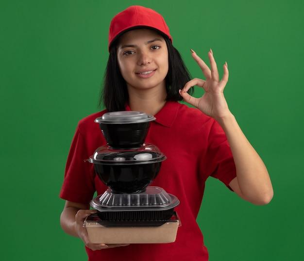 Glückliches junges liefermädchen in der roten uniform und in der kappe, die stapel von lebensmittelpaketen hält, die freundlich lächelnd zeigen ok zeichen, das über grüner wand steht