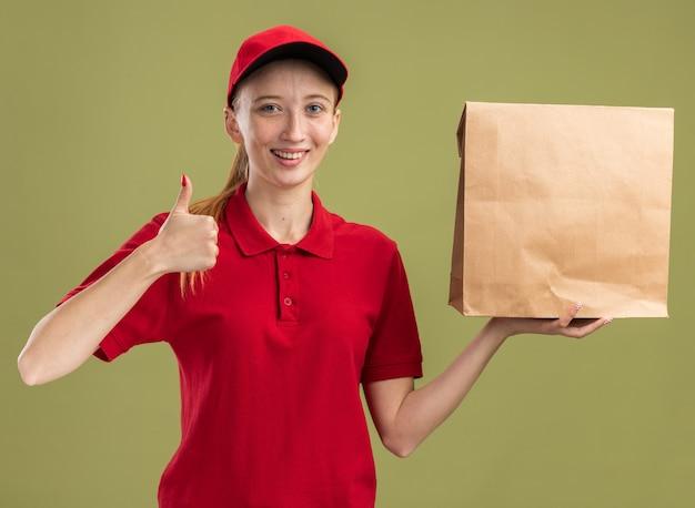 Glückliches junges liefermädchen in roter uniform und mütze, das paket hält, das zuversichtlich lächelt und daumen nach oben zeigt