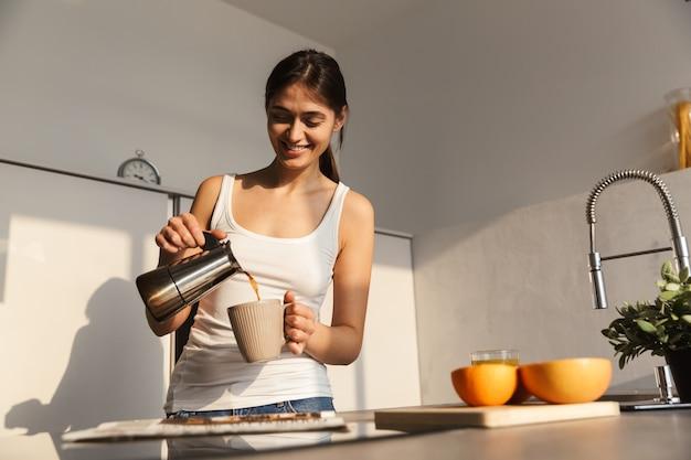 Glückliches junges mädchen, das am morgen in der küche steht und eine tasse kaffee trinkt