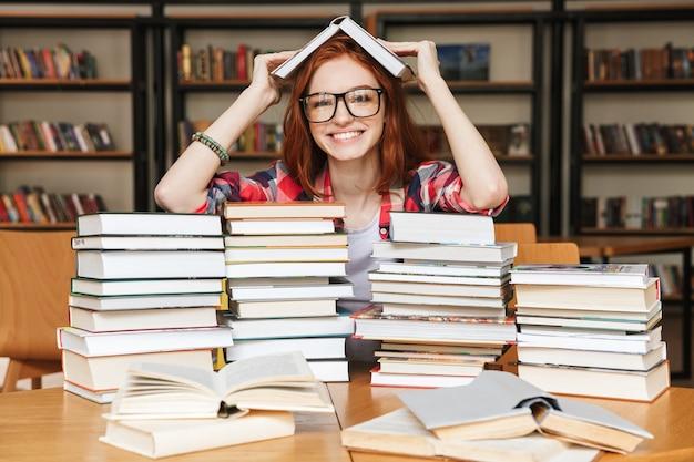 Glückliches junges mädchen, das an der bibliothek sitzt