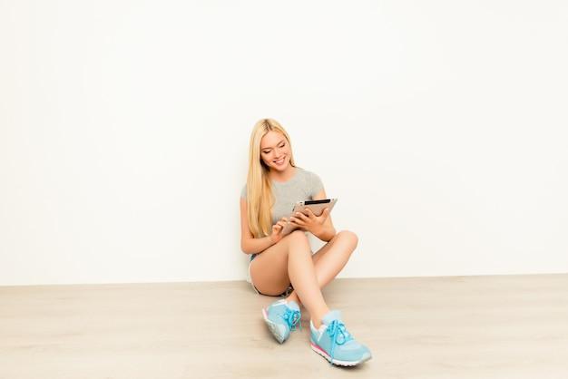 Glückliches junges mädchen, das auf boden sitzt und tablette benutzt