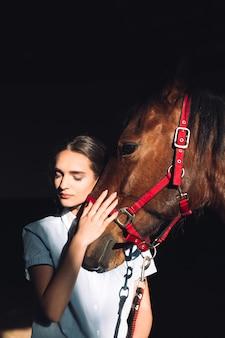 Glückliches junges mädchen, das draußen sitzt und ihr pferd umarmt
