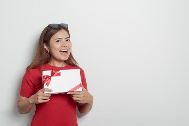 Glückliches junges mädchen, das ein weihnachtsgeschenk anhält