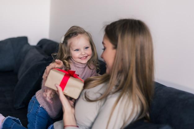Glückliches junges mädchen, das ihre mutter mit geschenk zu hause im wohnzimmer überrascht